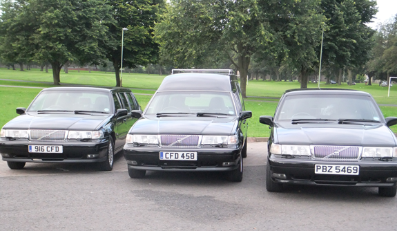 Hearse and limousines parked